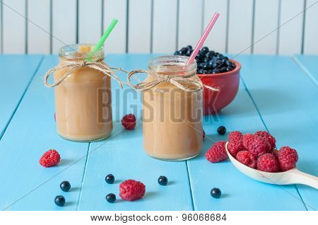 Baby food. Banana and apple puree with fresh raspberries, blueberries on lifht rural wooden backgrou