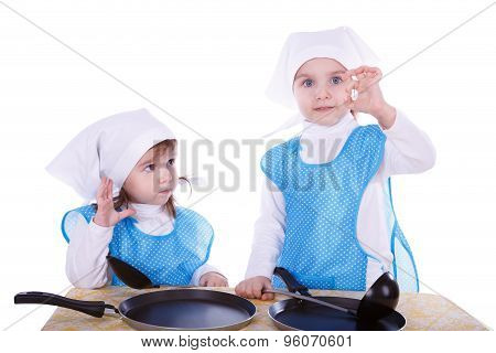 Little Children With Pans. Two Cute Girls Playing As Chefs. One Girl Gesturing Good Or Delicious. Is