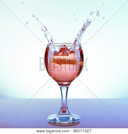 Glass Refreshing Rose Punch With Lemon Slice And Two Opposite Splashes