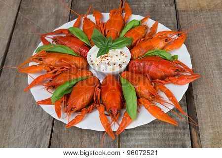 Plate With Red Boiled Crayfish And Herbs With White Sauce On The Side On A Wooden Table, Background