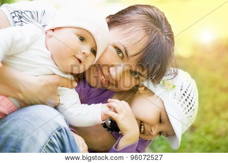 Young happy mother playing with two little children outside