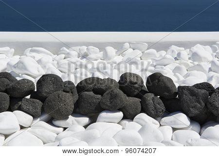 Black volcanic stones over white. Decoration detail at Santorini island