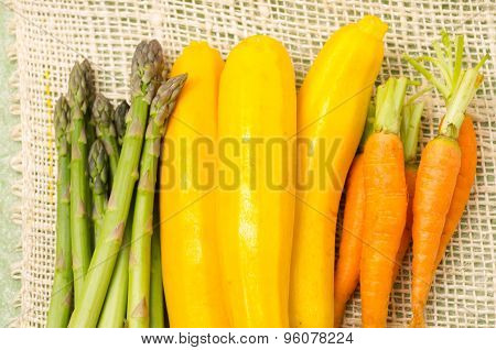 Bunch of brightly colored fresh asparagus, zucchinis and carrots in piles next to each other on a he