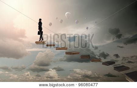 The girl rises upwards on a ladder from books