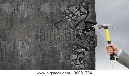 Close up of hammer in hand breaking cement wall