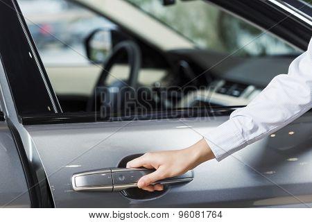 Close up of human hand opening door of car