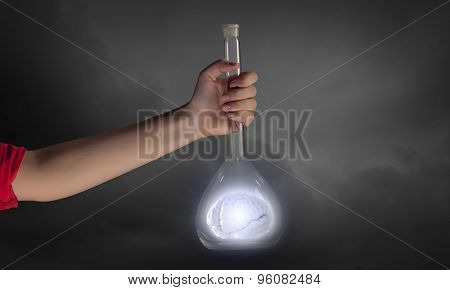 Hand holds flask with images on varied background