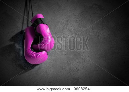 Boxing gloves hanging on nail on wall