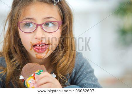 Greedy little girl eating chocolate