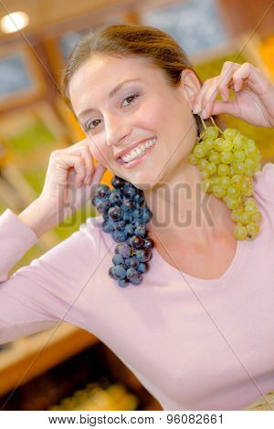 Woman using bunches of grapes as earrings