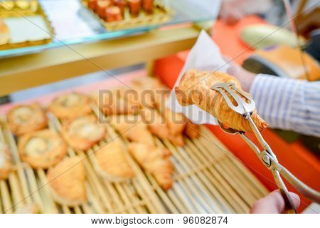 Croissant held in tongs