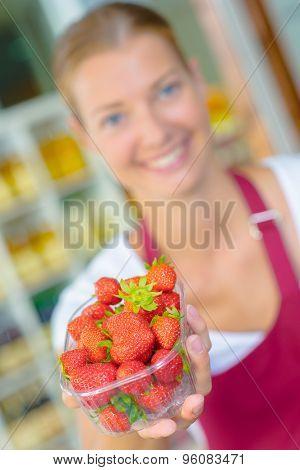 Supermarket worker holding some strawberries