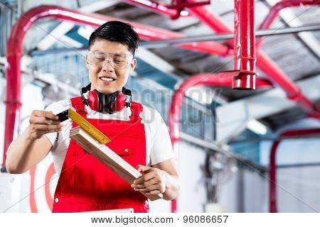 Asian Carpenter measuring piece of wood standing in factory or workshop