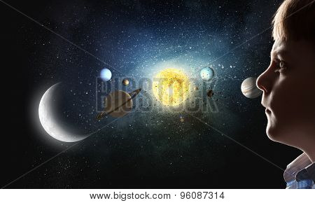 Cute boy of school age exploring space system