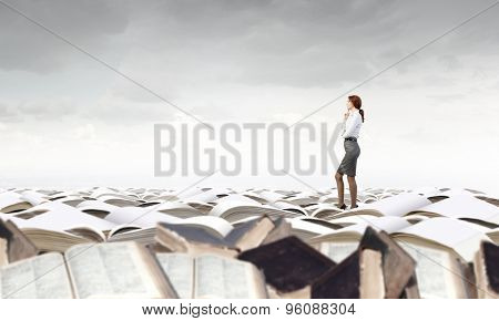 Pretty businesswoman standing on pile of books