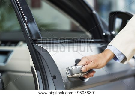 Close up of human hand opening door of car