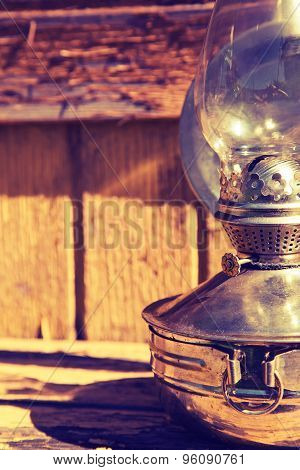 Old Kerosene Lamp On The Background Of Old Wooden Yellow Wall, Toning