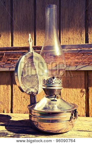 Old Kerosene Lamp Stands On Wooden Surface, Outdoors, Toning