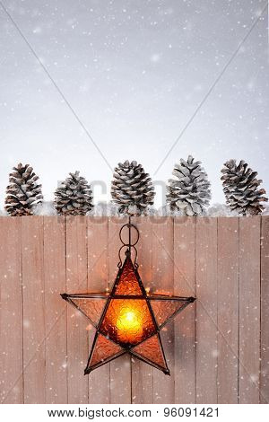 A star shaped lantern hanging on a rustic wood fence. Five pine cones are lined up on top of the fence on a winter evening with snow flakes.