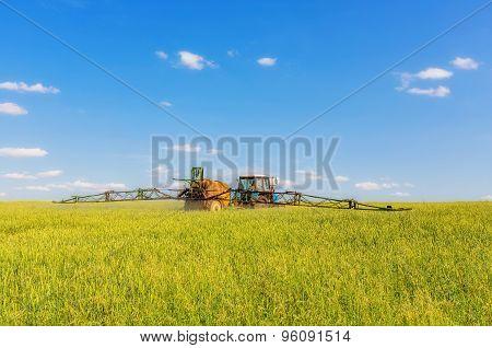 Farming Tractor Spraying Green Field