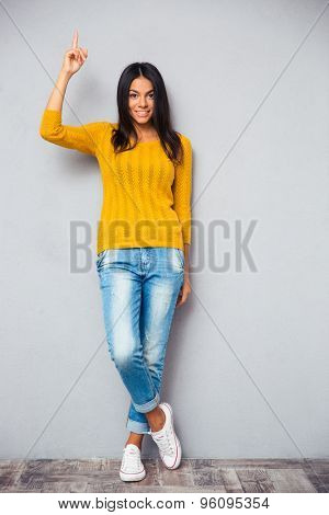 Full length portrait of a beautiful happy woman showing finger up over gray background. Looking at camera