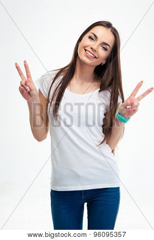 Happy young woman showing two fingers or victory gesture isolated on a white background. Looking at camera