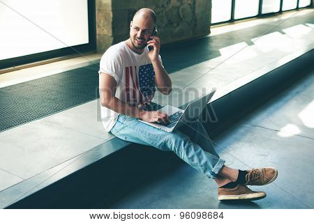 Male interior designer or young architect sitting in empty office working on a laptop and smartphone