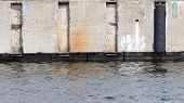 stock photo of rough-water  - gray old rough concrete wall with rust spots and stood out is reflected in the water on the waterfront - JPG