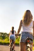 picture of pov  - Back view of two sporty beautiful young women on bikes wearing casual white tank tops and jeans shorts on park road on bright sunny summer day - JPG
