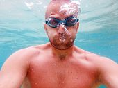 stock photo of goggles  - Man wearing goggles making bubbles below the surface of the sea underwater photography - JPG