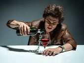 stock photo of alcoholic beverage  - Young man with bottle of alcohol  - JPG