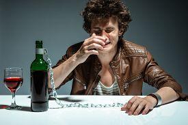 image of addicted  - Alcoholic drunk man drinking wine feeling depressed falling into addiction problem  - JPG