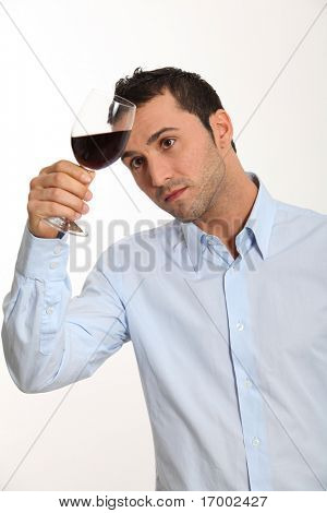 Young man on white background tasting red wine