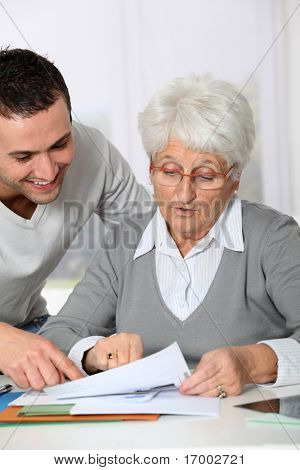 Young man helping elderly woman with paperwork