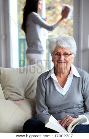Elderly woman reading book while housekeeper cleans windows