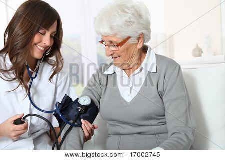 Closeup der Krankenschwester senior Woman Blutdruck überprüfen