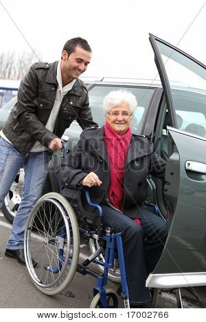 Young man assisting senior woman in wheelchair