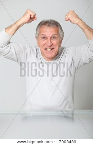 Senior man with arms up