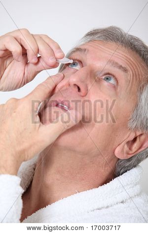 Senior man putting eye drops