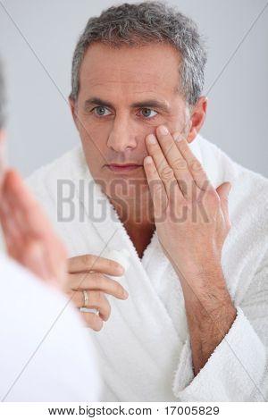 Portrait of mature man applying moisturizer on his face