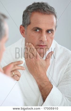 Portrait of mature man applying moisturizer on his face