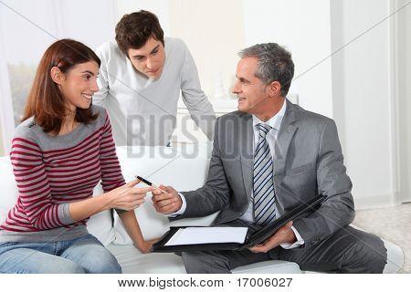 Pareja joven firma Alquiler de contrato con el agente de bienes raíces