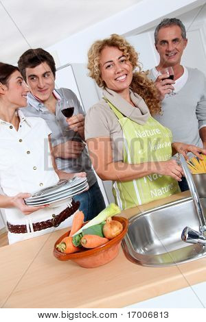 Group of friends preparing dinner in home kitchen