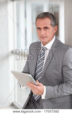 Hombre de negocios de pie en el pasillo con ficha electrónica