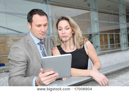 Business partners working on electronic pad
