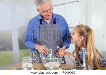 Grandfather with little girl preparing cake
