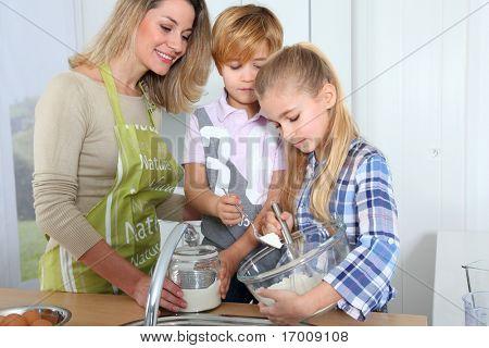 Mother and children in kitchen preparing cake