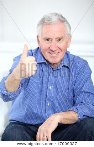 Portrait of smiling elderly man with thumb up