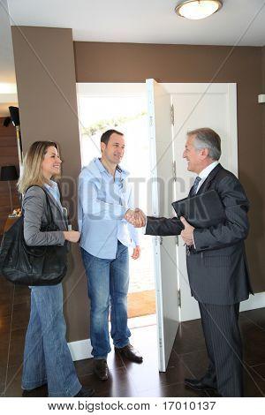 Casa moderna, agente de bienes raíces que muestra para pareja