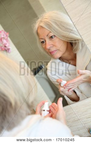 Senior woman applying moisturizer on her face